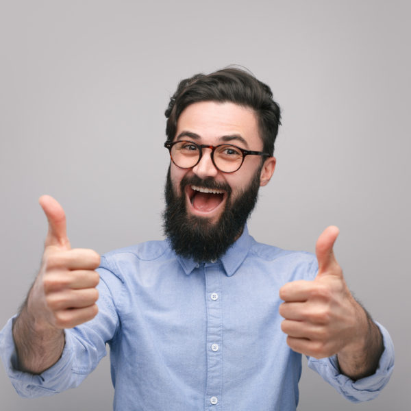 Content bearded man in shirt and glasses looking super excited holding thumbs up.